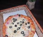 Small pizza with pork loin and olives