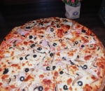 Family pizza with pork fillet, olives and fresh pepper