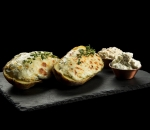 Stuffed potatoes with cheese, baked organic yellow cheese, butter, tartar sauce and cream