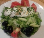 Lettuce with tomatoes, cucumbers on slices, olives and chopped egg