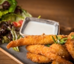Crispy chicken fillets with milk sauce and a mix of fresh salads