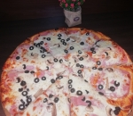Family pizza with ham, mushrooms and olives