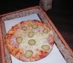 Small pizza with bacon and pickled cucumbers