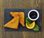 Crispy breaded yellow cheese with blueberry jam